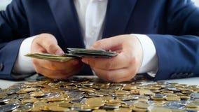 Begrepp av den giriga affärsmannen Ung man i dräktsammanträde på skrivbordet mycket av pengar och att räkna den stora bunten av s lager videofilmer