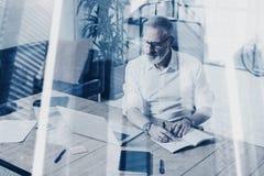 Begrepp av den vuxna lyckade affärsmannen som bär klassiskt exponeringsglas och arbete på den wood tabellen i modern coworking fotografering för bildbyråer