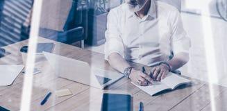 Begrepp av den vuxna lyckade affärsmannen som bär klassiskt exponeringsglas och arbete på den wood tabellen i modern coworking arkivfoton