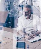 Begrepp av den vuxna lyckade affärsmannen som bär klassiskt exponeringsglas och arbete på den wood tabellen i modern coworking royaltyfri foto