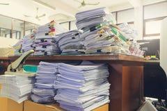 Begrepp av dokumentarbetsbördan, hög av oavslutade dokument på kontorsskrivbordet, bunt av affärspapper arkivbilder
