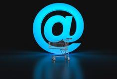 Begrepp av e-komrets Stort @ tecken och tom shoppingvagn på bla Arkivfoto