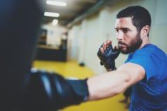 begrepp av en sund livsstil Övande sparkar för latinamerikansk muskulös mankämpe med att stansa den svarta påsen Sparkboxareboxni arkivfoto