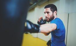 begrepp av en sund livsstil Övande sparkar för skäggig muskulös mankämpe med att stansa den svarta påsen Sparkboxareboxning Fotografering för Bildbyråer