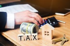 Begrepp av fastighetsskatter, köpet och försäljningen av egenskapen och huset inskrift royaltyfri foto