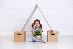 Begrepp av flyttningen och hus lycklig barnflicka med askar royaltyfri fotografi
