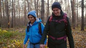 Begrepp av fotvandra och naturloppet Unga par av fotvandrare i skog på höst stock video