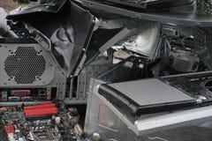 Begrepp av frihet från datorböjelse - mannen bryter systemenheten av en dator med en hummer utanför, sjön med royaltyfri bild