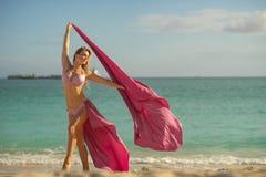 Begrepp av frihet och lycka Lycklig kvinna p? stranden i sommar med rosa silke f?r flyg royaltyfria foton