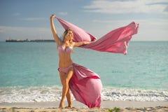 Begrepp av frihet och lycka Lycklig kvinna p? stranden i sommar med rosa silke f?r flyg royaltyfri foto