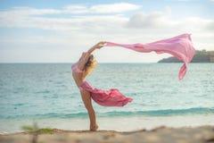 Begrepp av frihet och lycka Lycklig kvinna p? stranden i sommar med rosa silke f?r flyg royaltyfri fotografi