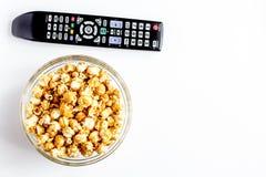 Begrepp av hållande ögonen på filmer med backgroun för vit för bästa sikt för popcorn Arkivfoton