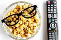 Begrepp av hållande ögonen på filmer med backgroun för vit för bästa sikt för popcorn Royaltyfri Foto