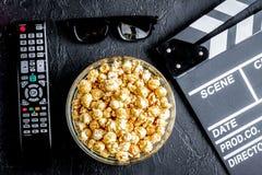 Begrepp av hållande ögonen på filmer med bakgrund för mörker för bästa sikt för popcorn royaltyfria bilder
