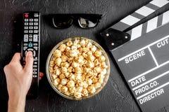 Begrepp av hållande ögonen på filmer med bakgrund för mörker för bästa sikt för popcorn royaltyfri bild