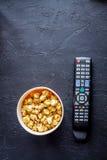 Begrepp av hållande ögonen på filmer med bakgrund för mörker för bästa sikt för popcorn Royaltyfri Foto