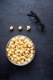 Begrepp av hållande ögonen på filmer med bakgrund för mörker för bästa sikt för popcorn Arkivbild