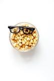 Begrepp av hållande ögonen på filmer med bakgrund för vit för bästa sikt för popcorn Arkivbilder