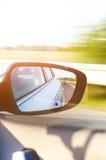 Begrepp av hastighet väg för bilkörning Reflexion i en bilspegel Spegelreflexion för bakre sikt oskarp bakgrund Arkivfoto