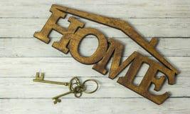 Begrepp av husförvärv, tangenten och ordhuset på en träbakgrund royaltyfria foton