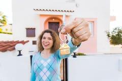 Begrepp av inflyttningsfest, fastighet, egenskap och flyttning - ny hem- ägare med nyckel- slut upp royaltyfri fotografi