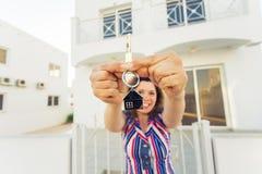 Begrepp av inflyttningsfest, fastighet, egenskap och flyttning - ny hem- ägare med tangent royaltyfri foto