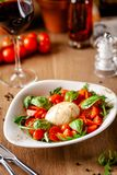 Begrepp av italiensk kokkonst Caprese sallad med körsbärsröda tomater, arugula- och basilikasalladblandning och mozzarellaost Por fotografering för bildbyråer