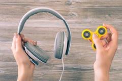 Begrepp av kombination som lyssnar till musik och använder den populära rastlös människaspinnaren Stäng sig upp fotoet av händer  royaltyfri foto