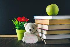 Begrepp av lärares dag Objekt på en svart tavlabakgrund Böcker grönt äpple, björn med ett tecken: Lyckliga lärares dag blyertspen Arkivbild