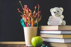 Begrepp av lärares dag Objekt på en svart tavlabakgrund Böcker grönt äpple, björn med ett tecken: Lyckliga lärares dag blyertspen Fotografering för Bildbyråer