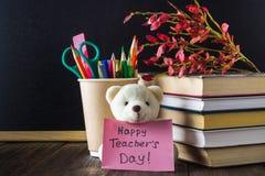Begrepp av lärares dag Objekt på en svart tavlabakgrund Böcker grönt äpple, björn med ett tecken: Lyckliga lärares dag blyertspen Arkivbilder