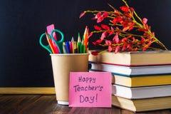Begrepp av lärares dag Objekt på en svart tavlabakgrund Böcker grönt äpple, platta: Lyckliga lärares dag, blyertspennor och penno Royaltyfri Bild