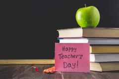 Begrepp av lärares dag Objekt på en svart tavlabakgrund Böcker grönt äpple, platta: Lyckliga lärares dag, blyertspennor och penno Royaltyfri Fotografi