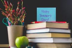 Begrepp av lärares dag Objekt på en svart tavlabakgrund Böcker grönt äpple, platta: Lyckliga lärares dag, blyertspennor och penno Royaltyfria Foton