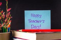 Begrepp av lärares dag Objekt på en svart tavlabakgrund Böcker grönt äpple, platta: Lyckliga lärares dag, blyertspennor och penno Fotografering för Bildbyråer