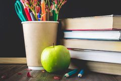 Begrepp av lärares dag Objekt på en svart tavlabakgrund Böcker grönt äpple, ritar, och pennor i ett exponeringsglas, fattar med h Royaltyfri Bild