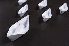 Begrepp av ledarskap i affär Origamipappersskepp seglar en efter andra på svart bakgrund äganderätt för home tangent för affärsid Royaltyfria Bilder