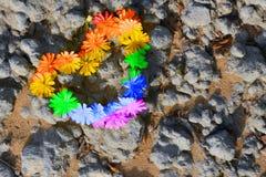 begrepp av LGBT regnbågen färgad hjärta av blommor på en sandsten vaggar bakgrund arkivfoto