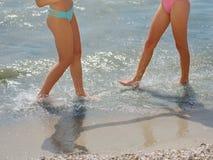 Begrepp av loppet - kvinnabencloseup som går på vit sand som kopplar av i strandkläder för strandtäckmantelpareo royaltyfria bilder