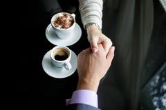 Begrepp av man- och kvinnlighänder, förälskelse och kaffe Arkivfoto