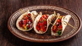 Begrepp av mexicansk kokkonst Mexicanska aptitretaretaco med grönsaker, bönor, paprika, chilipeppar på stekt osyrat bröd arkivbild