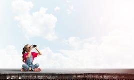 Begrepp av oförsiktig lycklig barndom med flickan av skolaåldern som ser i framtid fotografering för bildbyråer
