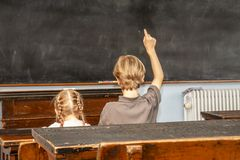 Begrepp av offentlig grundskola för barn mellan 5 och 11 årutbildning med ungt pojke- och flickasammanträde i klassrumet royaltyfri fotografi