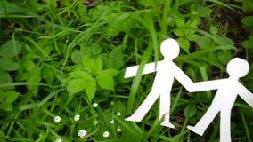 Begrepp av personen och miljön Människadiagram som göras av papper på gräs Horisontalanvända för panoramaultrarapidkamera lager videofilmer