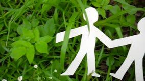 Begrepp av personen och miljön Människadiagram som göras av papper på gräs Panoramaultrarapidkamera genom att använda Steadicam lager videofilmer