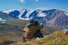 Begrepp av resanden med hunden i bergen Man med Siberian skrovliga blickar på dekorkade bergen tillbaka sikt royaltyfri fotografi