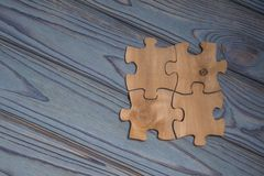 Begrepp av samlade stycken av pussel på den wood texturbakgrunden Royaltyfri Bild