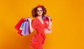 Begrepp av shoppingköp och försäljningar av den lyckliga flickan med packar på gul bakgrund royaltyfria foton
