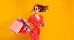 Begrepp av shoppingk?p och f?rs?ljningar av den lyckliga unga flickan med packar p? gul bakgrund royaltyfri foto