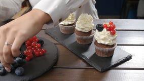 Begrepp av små och medelstora företag och konfekt Kvinnlig bagare som dekorerar den smakliga muffin stock video